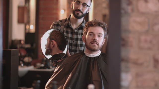 barber in hairdresser showing client hair cut - real people stock videos & royalty-free footage