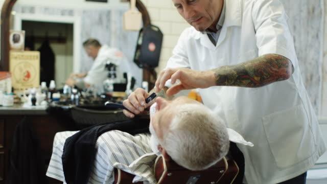 vidéos et rushes de effectuer le rasage avec le rasoir de coiffeur - miroir ancien