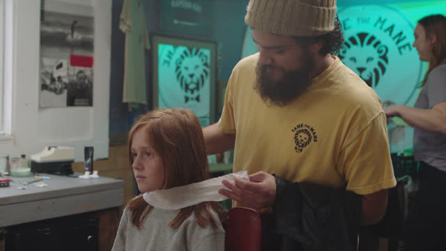 vídeos de stock e filmes b-roll de a barber places a booster seat down for a younger customer - cut video transition