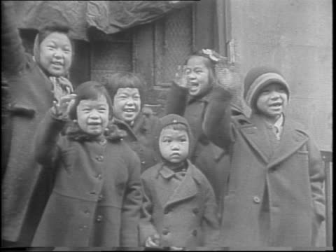 barber placing chinese and american flags over shop entrance / chineseamerican girl fixes another child's hair / two men hold chinese and american... - first lady stock-videos und b-roll-filmmaterial