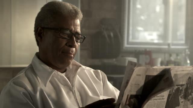 vídeos y material grabado en eventos de stock de barber reading newspaper, removing glasses, thinking. - un solo hombre mayor
