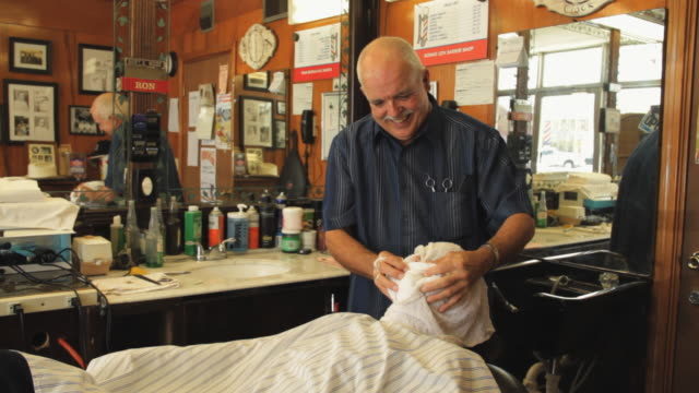 ms barber removing hot towel from client's face / madison, florida, usa - barber shop stock videos and b-roll footage