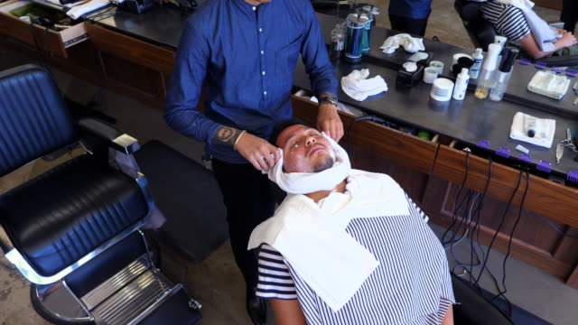 MS HA Barber removing towel from mans face before shave in barber shop