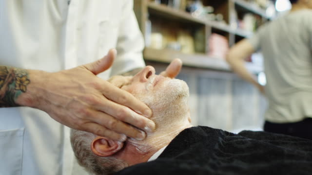 Barber Rubbing Client's Face