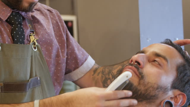 Barber shaves customer with straight razor blade