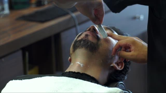 barber shaves the beard of the client - peluria del viso video stock e b–roll