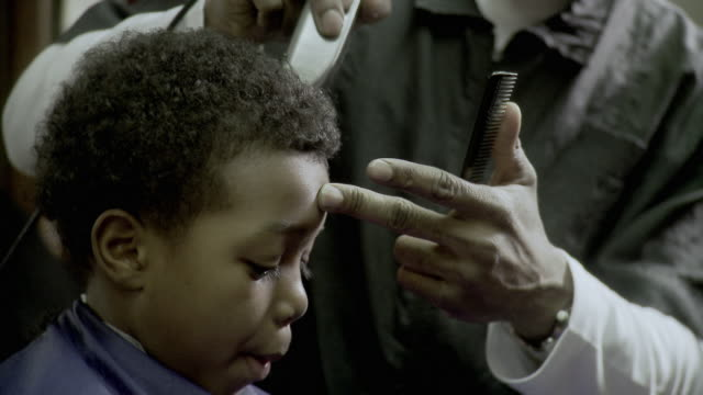 stockvideo's en b-roll-footage met cu r/f tu td barber shaving boy's (8-9) hair at barbershop, brooklyn, new york city, new york state, usa - menselijk haar