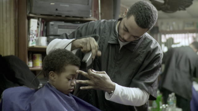 ms barber shaving boy's (8-9) hair at barbershop, brooklyn, new york city, new york state, usa - barber stock videos & royalty-free footage