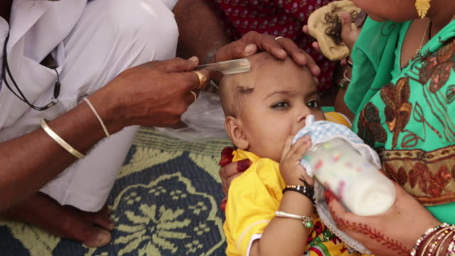 barber shaving head of a baby, haridwar, uttarakhand, india - ceremony stock videos and b-roll footage