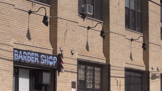 Barber Shop exterior in Brooklyn on a sunny day.