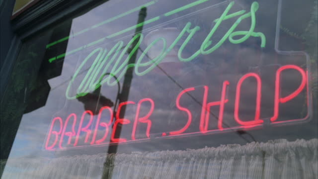 cu la barber shop neon sign with reflections in window - shop sign stock videos & royalty-free footage