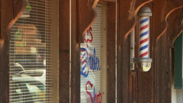 cu barber shop with carved, rustic wooden door and traditional spinning barber pole / wyoming, usa - barber shop stock videos & royalty-free footage