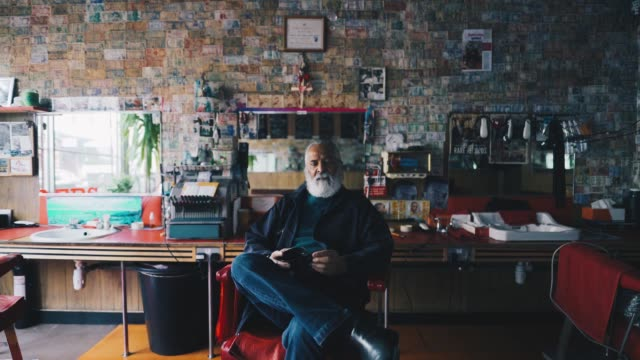 Barber sitting down in his shop
