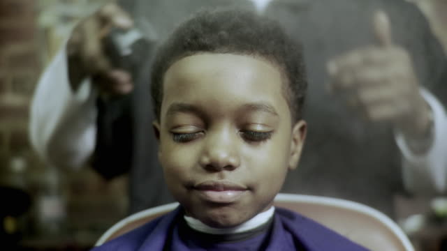 stockvideo's en b-roll-footage met cu barber spraying boy's (8-9) hair with hair product at barbershop, brooklyn, new york city, new york state, usa - afro amerikaanse etniciteit