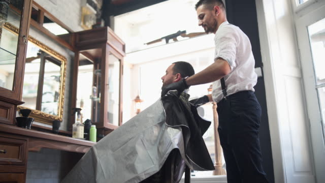 barber spreading cape on customer in salon - barber chair stock videos & royalty-free footage