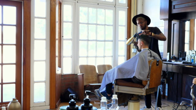 MS Barber styling clients hair with blow dryer after hair cut in barber shop