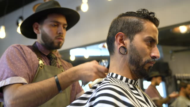 barber styling customer's hair with electric razor - stile di capelli video stock e b–roll