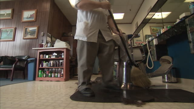 ms la barber sweeping up hair off floor at barber shop / rutland, vermont, usa - sweeping stock videos & royalty-free footage