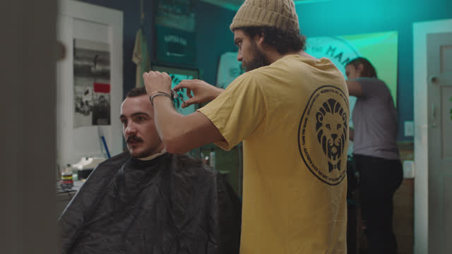 vídeos de stock e filmes b-roll de a barber talks to his customer as he cuts his hair - cut video transition