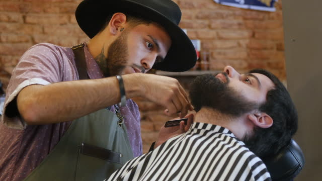 barber trimming beard of customer in hair salon - hair length stock videos and b-roll footage