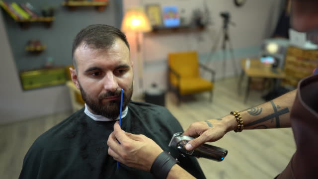 barber trimming client's facial hair with electric razor at barber shop - cutting hair stock videos & royalty-free footage