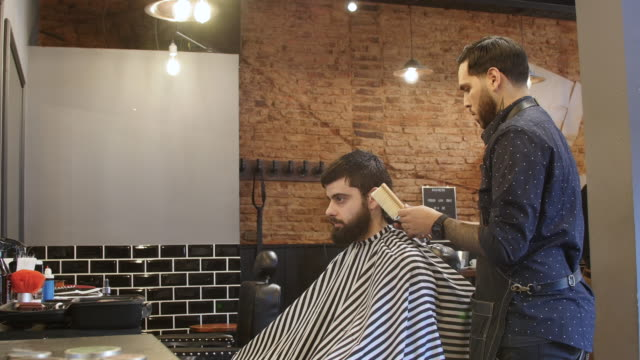 barber trimming client's hair using electric razor - barber shop stock videos & royalty-free footage