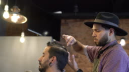Barber trimming client's hair using tools in shop
