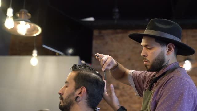 barber trimming client's hair using tools in shop - etnia latino americana video stock e b–roll