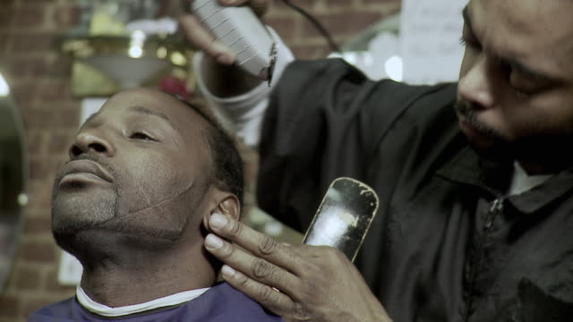 cu barber trimming customer's facial hair at barbershop, brooklyn, new york city, new york state, usa - ärr bildbanksvideor och videomaterial från bakom kulisserna