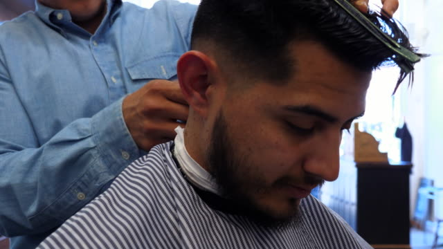 ms barber trimming mans hair in barber shop - hair clipper stock videos & royalty-free footage