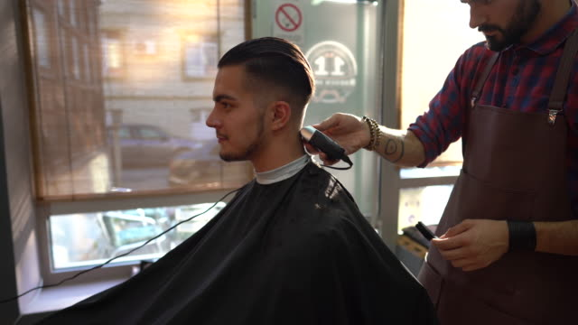 barber trimming man's hair with electric razor in barber shop - cutting hair stock videos & royalty-free footage