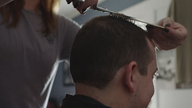vídeos de stock e filmes b-roll de a barber trims the sides and top of a man's hair - cut video transition