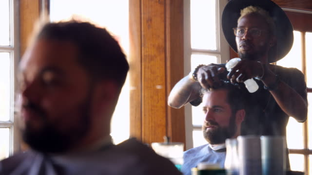 ms barber using product to style mans hair in barber shop - hairdresser stock videos & royalty-free footage