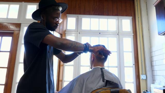 ms tu barber using scissors to cut mans hair in barber shop - haare schneiden stock-videos und b-roll-filmmaterial