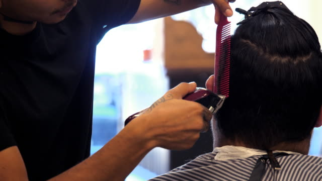 ms td barber using trimmer while cutting clients hair in barber shop - hair clipper stock videos & royalty-free footage