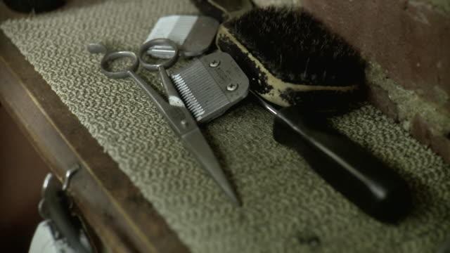 vídeos de stock, filmes e b-roll de ecu selective focus barber's scissors, clippers blade and brush on table top, brooklyn, new york city, new york state, usa - tesoura