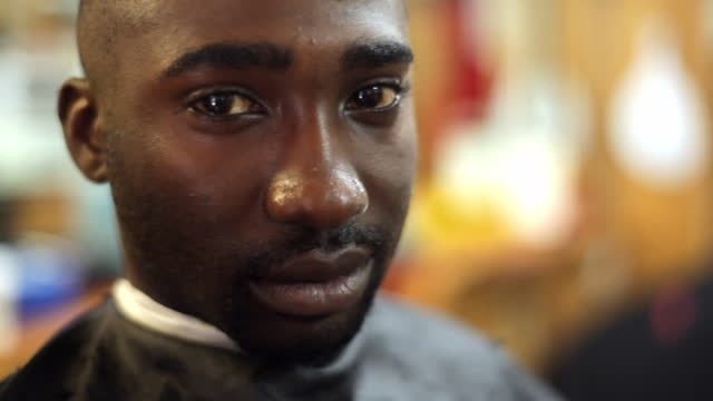 A barbershop customer looks seriously at the camera.