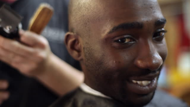 A barbershop customer smiles while getting his head shaved.