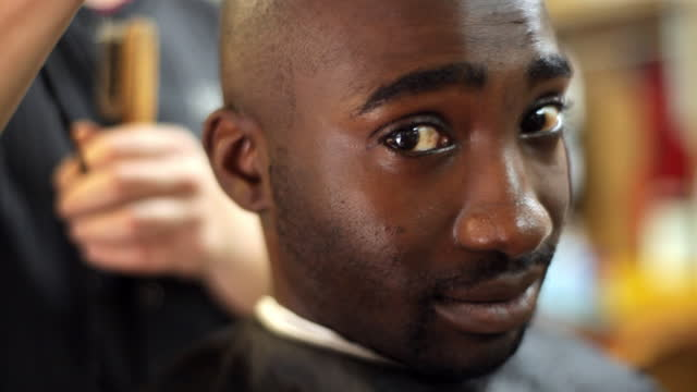 a barbershop customer smiles while getting his head shaved. - shaving stock videos & royalty-free footage