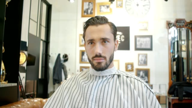 barbershop - young attractive man getting his hair cut at the barber - barber shop stock videos and b-roll footage