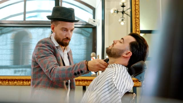 barbershop - young barber styling a business man - barber shop stock videos & royalty-free footage