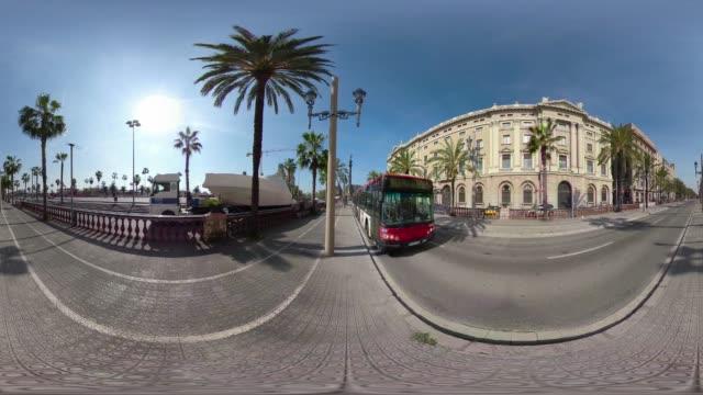 barcelona 360 degree video bus crossing columbus promenade walkway. vr equirectangular panorama - 360 grad panorama stock-videos und b-roll-filmmaterial