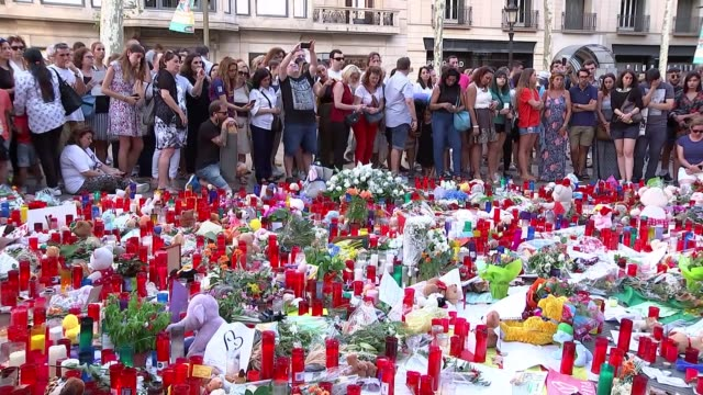 search for suspected van driver contiues SPAIN Barcelona EXT People looking at floral tributes for victims of Barcelona terror attack Lit candles...