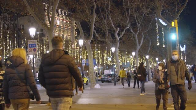 vídeos de stock e filmes b-roll de barcelona christmas at night. people wearing masks walking along paseo de gracia boulevard - centro da cidade