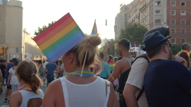 barcelona gay pride parade. woman with rainbow flags - aktivist stock-videos und b-roll-filmmaterial