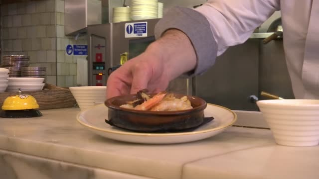 Barcelona in London for Champions League game against Chelsea ENGLAND London Casa Brindisa INT Chef placing plate onto counter and sprinkling salt