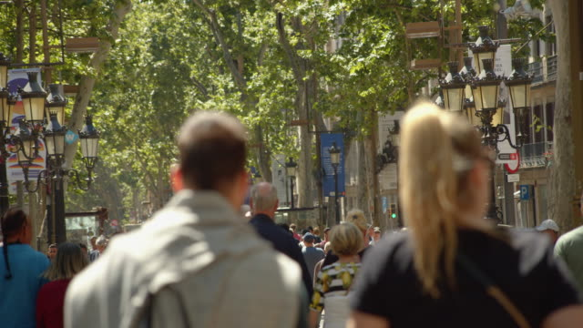 barcelona ramblas crowded in slow motion. famous street establishing shot filmed slow motion with telephoto lens with defocused crowd - telephoto lens stock videos and b-roll footage