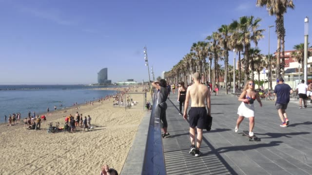 vídeos de stock, filmes e b-roll de barcelona residents spend the morning at the beach, walking, exercising, while bathing is only allowed for federated athletes and sunbathing is still... - espanha