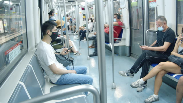 vídeos de stock e filmes b-roll de barcelona subway new normal during coronavirus crisis. people wearing masks at train interior during covid-19, summer 2020 - transportation
