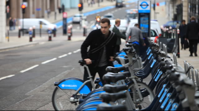barclays cycle hire scheme, or borris bikes, part of a green initiative by transport for london. this docking station at southwark is one of many around the capital city where people, once registered can take a bike free for half an hour(charges apply afte - mayor stock videos & royalty-free footage
